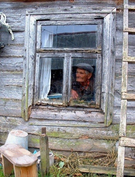1637007-the-old-man-in-the-window-of-an-old-house.jpg