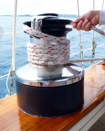 cutcaster-photo-100240388-Pulling-the-rope-tight-on-a-sailboat-winch.jpg