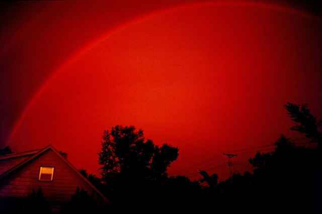 A monochrome rainbow in a red sky